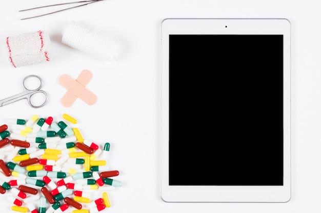 Пустой цифровой планшет с медицинскими расходными материалами и оборудованием на белом фоне Бесплатные Фотографии