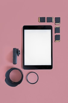 Blank digital tablet with memory cards and camera accessories on colored background