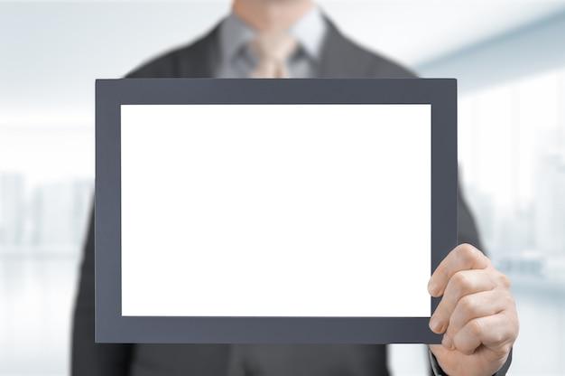빈 졸업장 또는 인증서를 사업가 손에 모의. 복사 공간을 가진 빈 사진 프레임 테두리입니다. 사무실에서 복사 공간을 가진 빈 프레임을 들고 사업