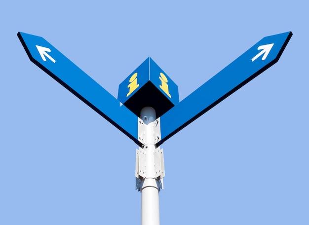 Пустые направленные дорожные знаки над голубым небом