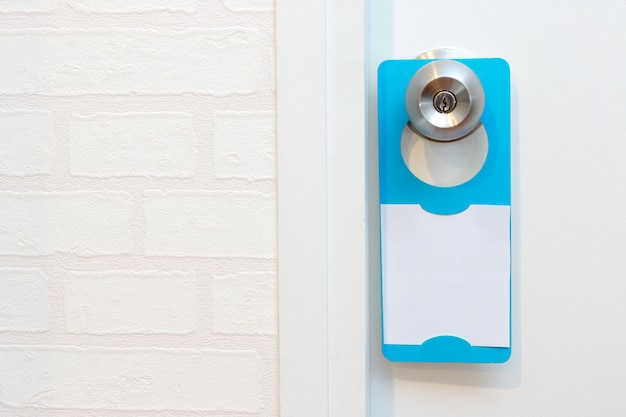 A blank door hanger on a door, with copy space, add text or graphic