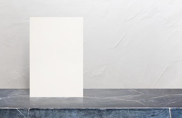 Blank eco textured paper poster on marble stone table top at white wall background.