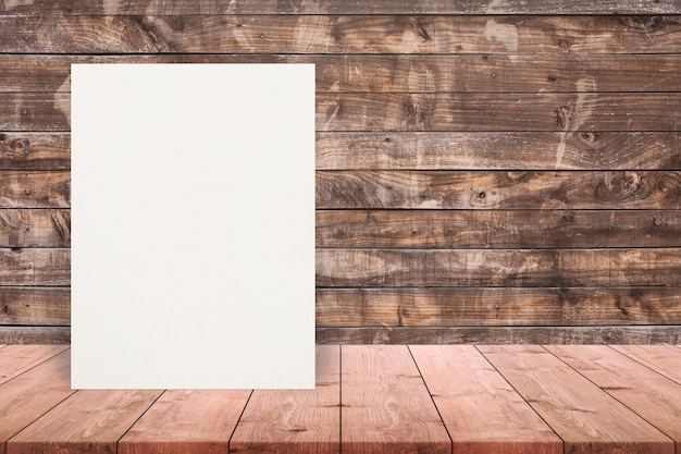 Blank eco textured paper poster on wood table top at old wooden wall