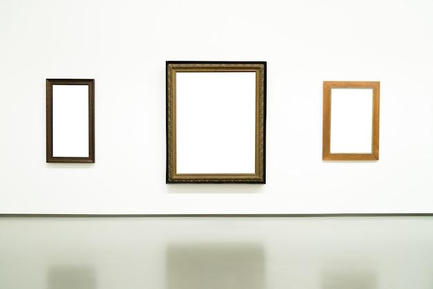 展示会で壁に空白の空の金色の絵画フレーム。