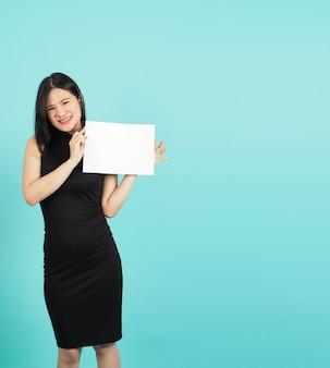 Пустой лист бумаги в руке девочки-подростка или женщины на зеленом или синем фоне тиффани. она носит черное платье