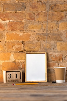 Blank empty picture or sheet on the brown brick wall with coffee cup and pencils. 31 of december, new year concept.