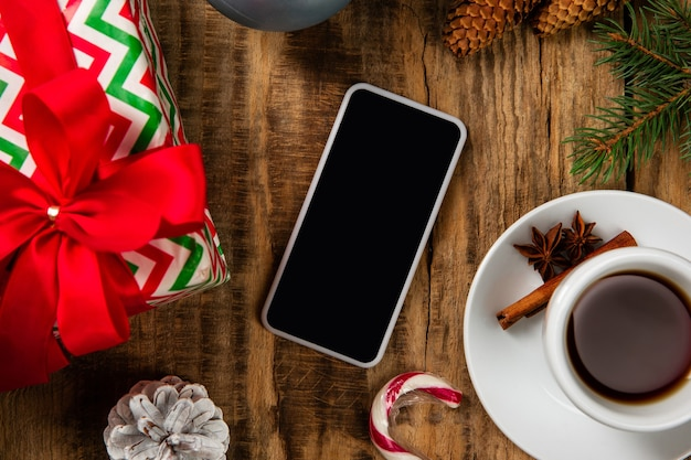 Blank empty screen of smartphone on the wooden wall with colorful holiday's decoration, tea and gifts.