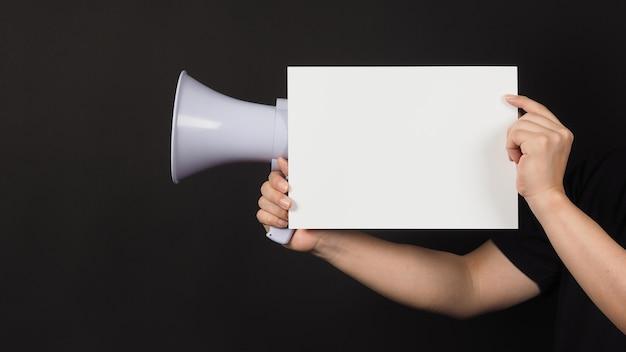 Пустая пустая белая доска в мужской руке и мегафон на черном фоне.