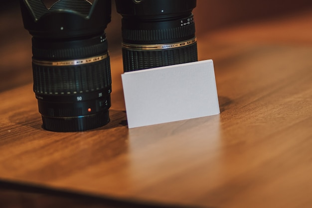 Blank empty white business cards next to camera lenses