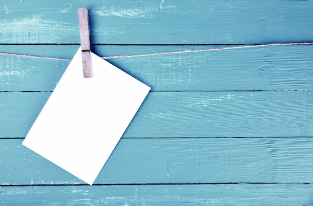 Blank envelope hanging on rope on wooden clothespin