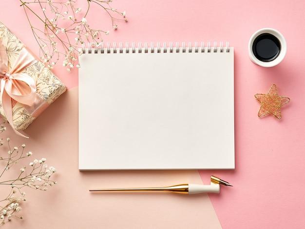 書道ペン、インク、花、プレゼントとピンクまたはベージュの背景の空白の封筒。上からの眺め。