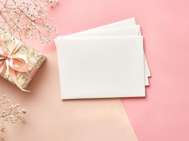 花とプレゼントのピンクまたはベージュの背景の空白の封筒。上からの眺め。