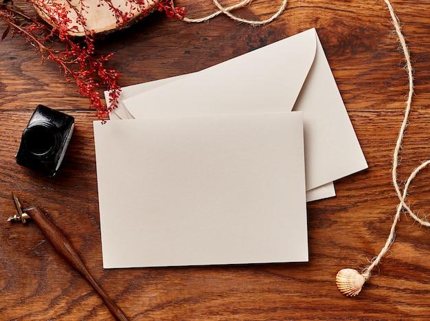 書道ペンとインクで木製の背景の空白の封筒。上からの眺め。