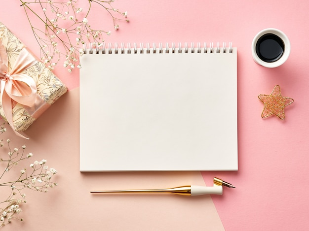 Blank envelopes on pink or beige background with calligraphy pen, ink, flowers and present. view from the top.