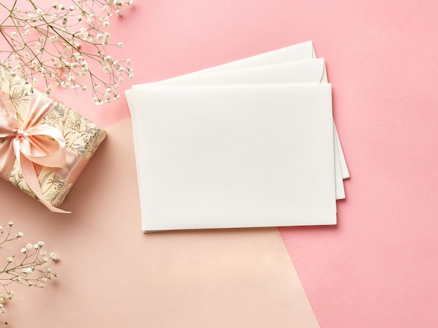 Blank envelopes on pink or beige background with flowers and present. view from the top.