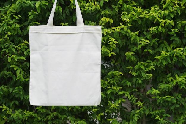 Blank fabric bag hanging on green leaf