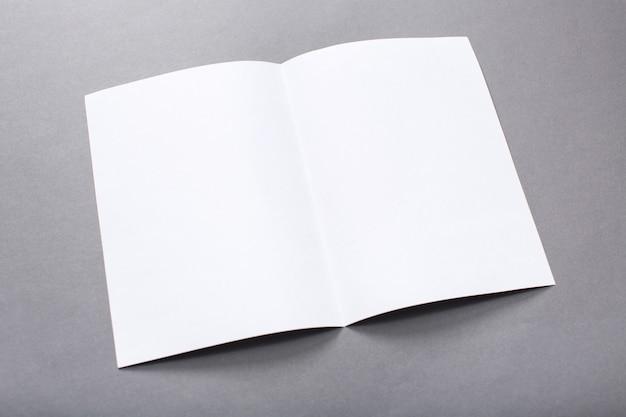 Пустой сложенный флаер, изолированный на сером, с обтравочным контуром