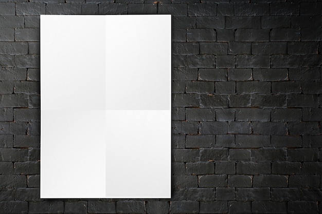 Blank folded paper poster hanging on black brick wall