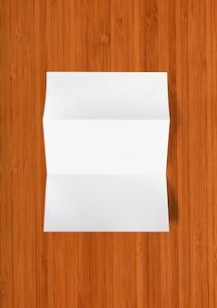 Чистый сложенный лист бумаги а4, изолированные на темной деревянной поверхности