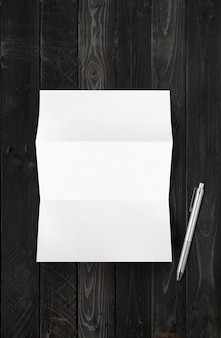 Blank folded white a4 paper sheet mockup and pen isolated on black wood background