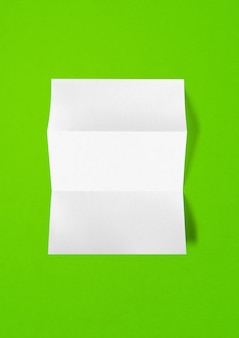 Blank folded white a4 paper sheet mockup template isolated on green background
