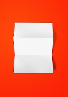 Blank folded white a4 paper sheet mockup template isolated on red background