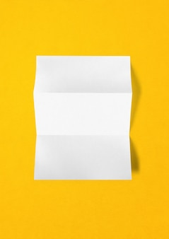 Blank folded white a4 paper sheet mockup template isolated on yellow background