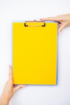 Пустая папка с желтой бумагой, рука, которая держит папку и ручка на белом