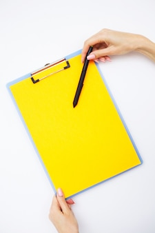 Blank folder with yellow paper. hand that holding folder and handle on white background.