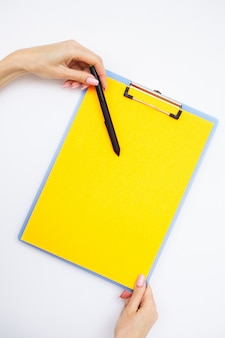 Blank folder with yellow paper, hand that holding folder and handle on white