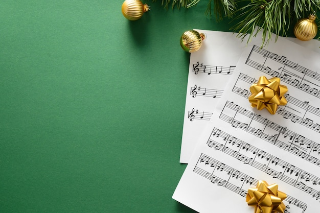 Заготовка для рождественских гимнов и поет, украшенные золотыми шарами на зеленом