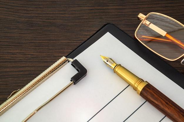 空白のフォームと茶色の木製のテーブルのレポートを作成するためのペン
