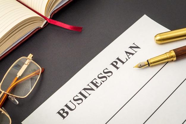 空白のフォームとペン、メガネ、ビジネスプランを作成するためのメモ帳