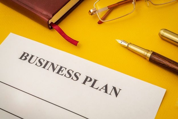 Blank form, glasses and pen for drawing up business plan on yellow table