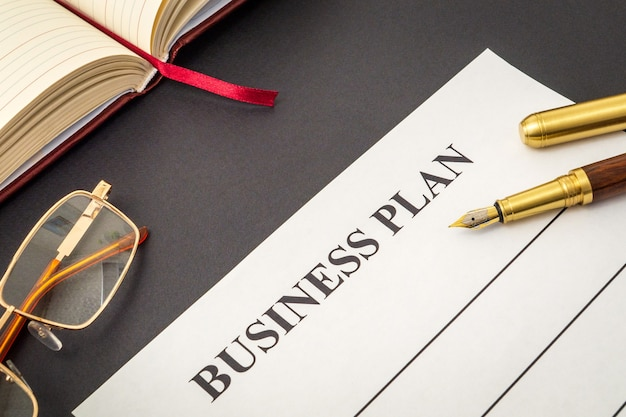 Blank form and pen, glasses, notepad for drawing up business plan