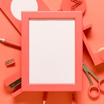 Пустая рамка и розовые канцтовары на цветной поверхности