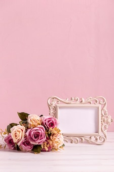 Blank frame and beautiful rose bouquet