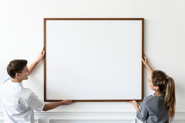 Blank frame being hung by a couple