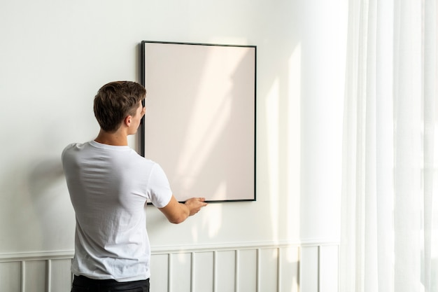 Cornice vuota appesa da un giovane su un muro minimo bianco