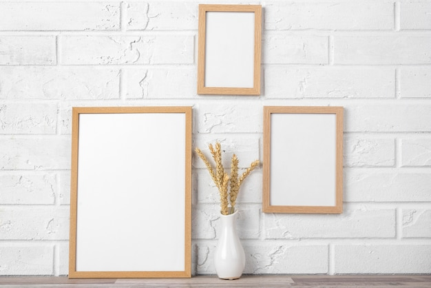 Blank frame collection on wall and next to vase