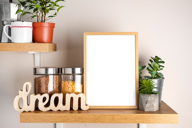 Blank frame next to flower pot and jar with condiments
