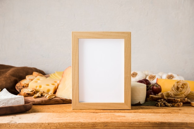 Blank frame in front of cheese and ingredient on wooden table