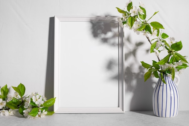Blank frame mockup with cherry tree blossoms in vase on table
