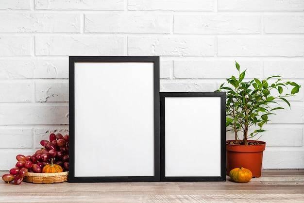 Пустая рамка рядом с цветочным горшком и виноградом