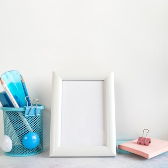 Blank frame and office tools on desk