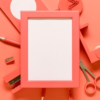 Blank frame and pink stationery on colored surface