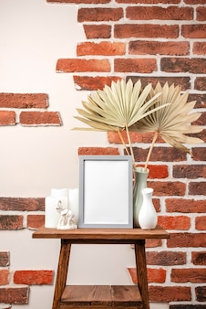 Blank frame on shelf beside vase with dry leaves