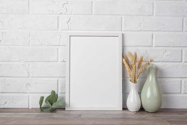 Blank frame on shelf beside vase