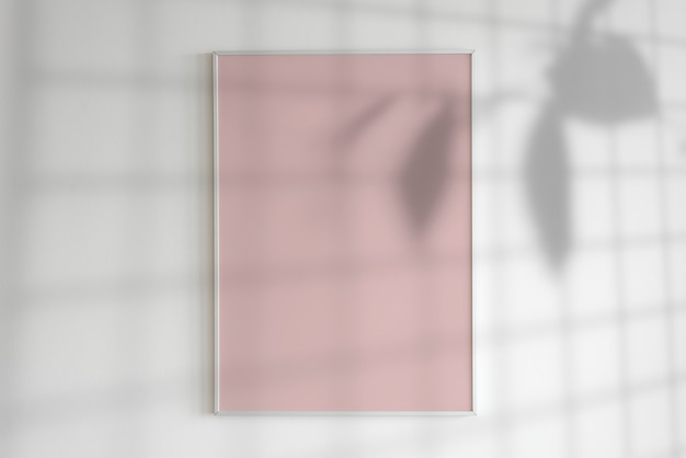 Blank frame on a wall with plant shadow