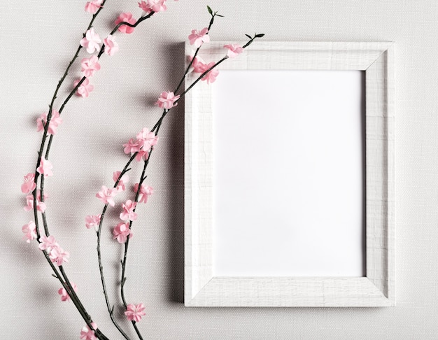 Blank frame with beautiful flowers beside